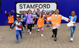 FULHAM, ENGLAND - AUGUST 16: Children pose in front of Stamford Bridge during the Chelsea Foundation Active Family Event sponsored by Rexona at Eel Brook Common on August 16, 2019 in Fulham, England. (Photo by Clive Howes - Chelsea FC/Chelsea FC via Getty Images)